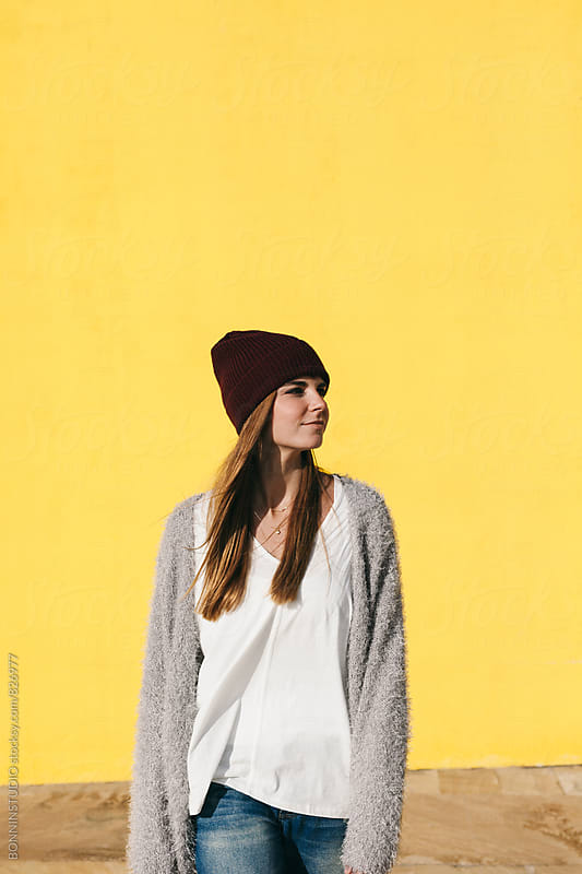 Caucasian woman walking in front of a yellow wall. by BONNINSTUDIO for Stocksy United