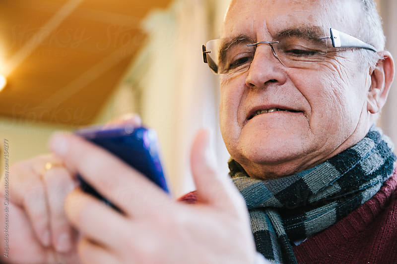 Senior man using smartphone smiling. Grandfather learning new technologies by Alejandro Moreno de Carlos for Stocksy United