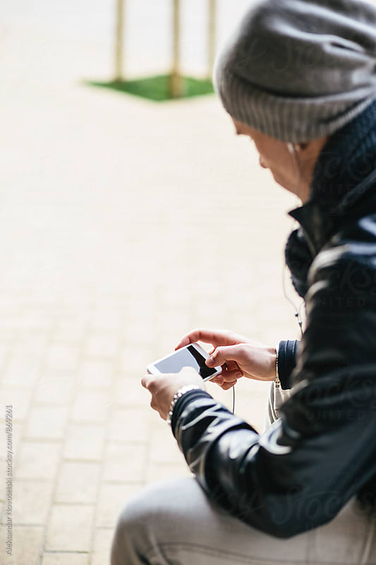 Young man with hat, using his smartphone in urban environment by Aleksandar Novoselski for Stocksy United