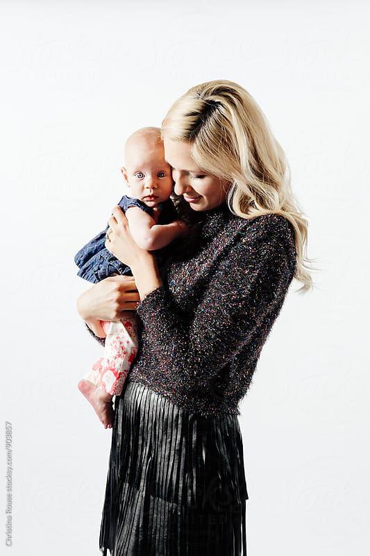 Cute baby girl looks at camera while held by mother by Christina Rouse for Stocksy United