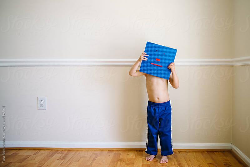 little boy hides face behind a blue emoticon building block face by Tara Romasanta for Stocksy United
