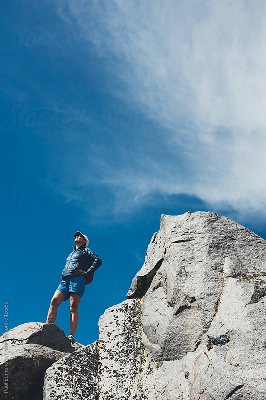 Female hiker standing on rocky mountain summit by Paul Edmondson for Stocksy United