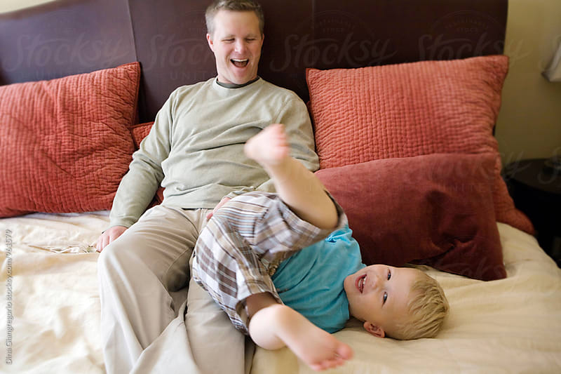 Dad and Son Playing On Bed by Dina Giangregorio for Stocksy United