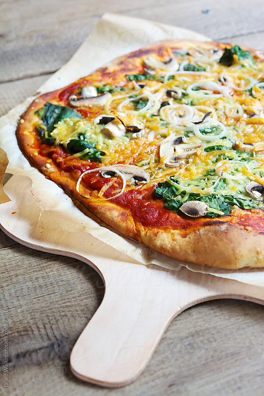 Spinach-mushroom pizza (vegan) by Harald Walker for Stocksy United