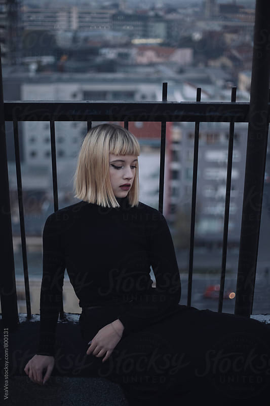 Blonde stylish woman on the roof of the building during sunset  by Marija Mandic for Stocksy United