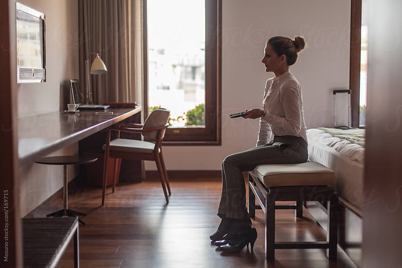 Businesswoman Watching TV in a Hotel Room by Mosuno for Stocksy United