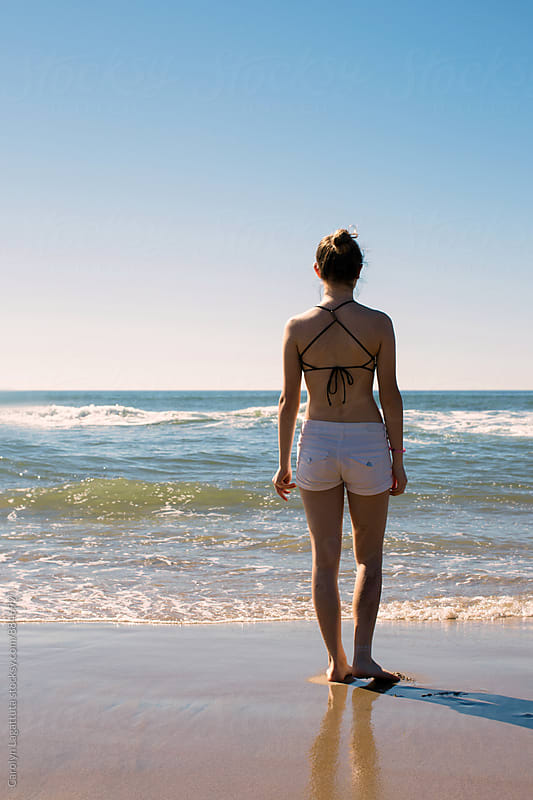 Teenage girl facing the ocean in shorts and a bikini top on a sunny, clear day by Carolyn Lagattuta for Stocksy United