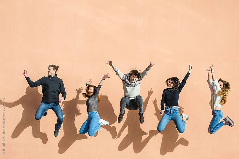 Group of teenage friends jumping in front of a wall. by BONNINSTUDIO for Stocksy United