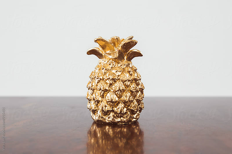 Small golden pineapple on a wooden table by Vera Lair for Stocksy United