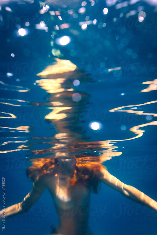 Naked female swimming by Nikola Bradonjic for Stocksy United