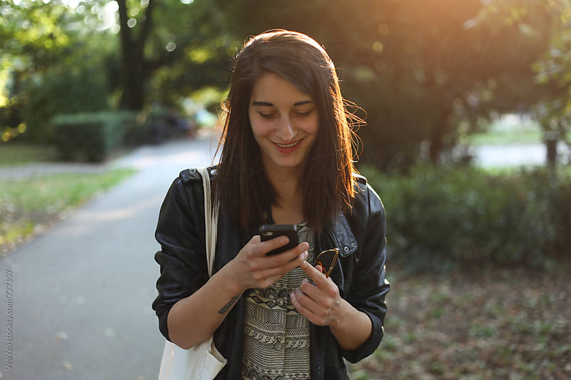 Woman using her mobile phone and smiling in the park by VeaVea for Stocksy United