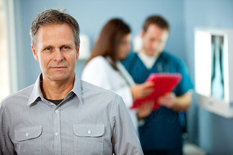 Exam Room: Serious Male Patient in Exam Room by Sean Locke for Stocksy United