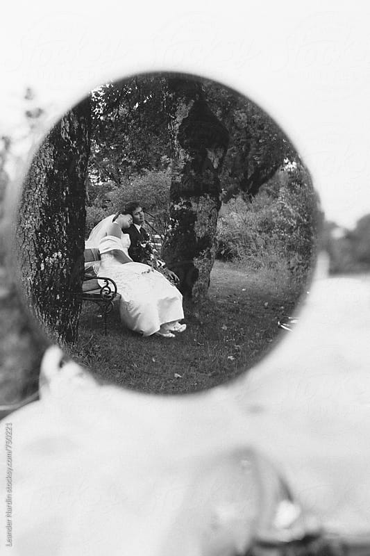 bridal couple sitting on a bench, seen in a rearview mirror from an classic oldtimer in black and white by Leander Nardin for Stocksy United