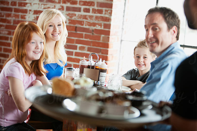 Barbeque: Waiter Brings Dinner to Family Table by Sean Locke for Stocksy United