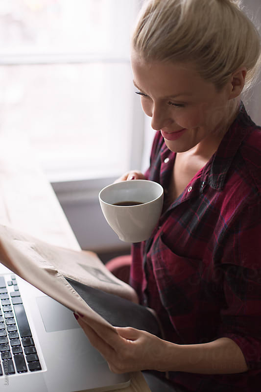 Happy Woman Reading the Newspaper and Drinking Coffee by Lumina for Stocksy United