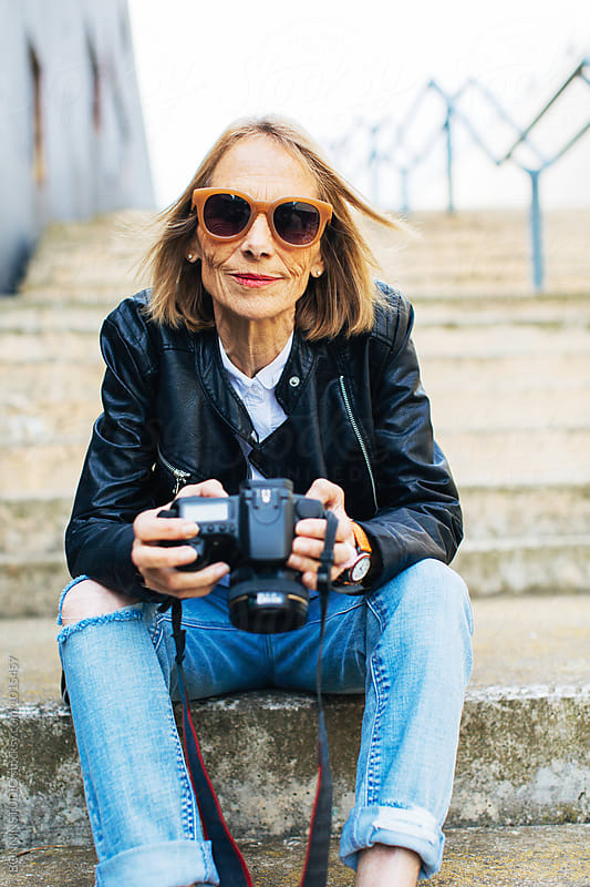 Portrait of a mature woman holding her camera sitting on stairs.  by BONNINSTUDIO for Stocksy United
