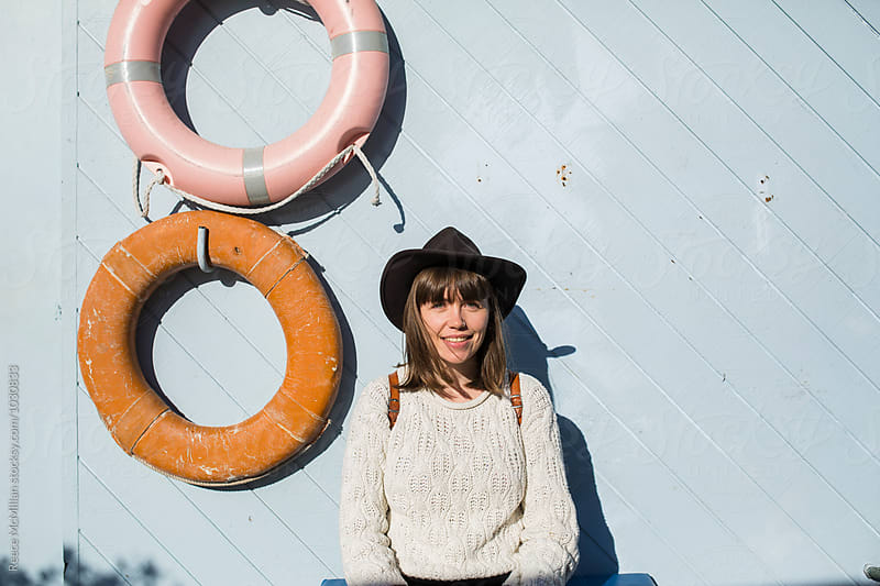 A cute girl sits against a marina building wall by Reece McMillan for Stocksy United