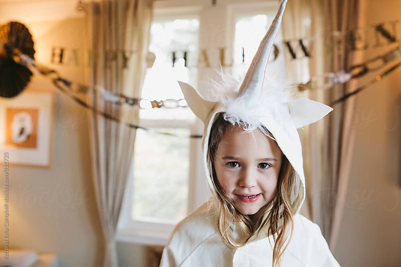 Girl in unicorn costume staring at camera - content by Rob and Julia Campbell for Stocksy United