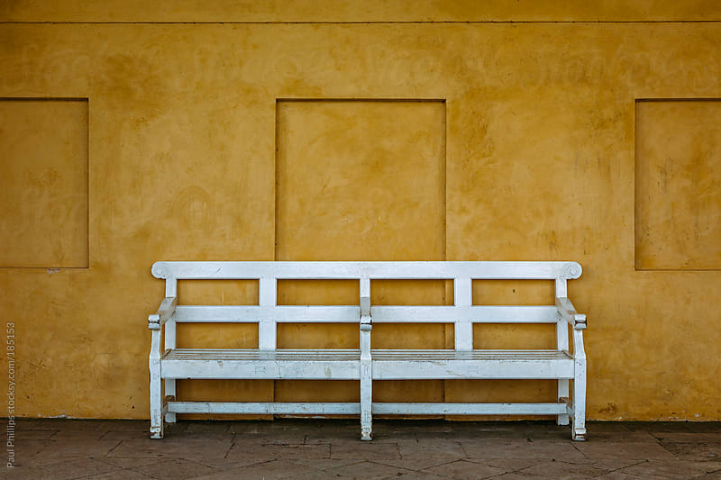 White bench against an antique orange wall  by Paul Phillips for Stocksy United