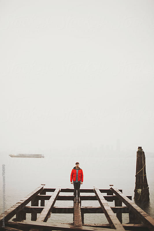 man in red coat on an old bridge by Sam Hurd Photography for Stocksy United