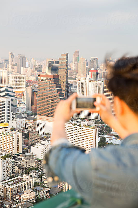 Young man taking picture with smartphone on city view during vacation by Jovo Jovanovic for Stocksy United