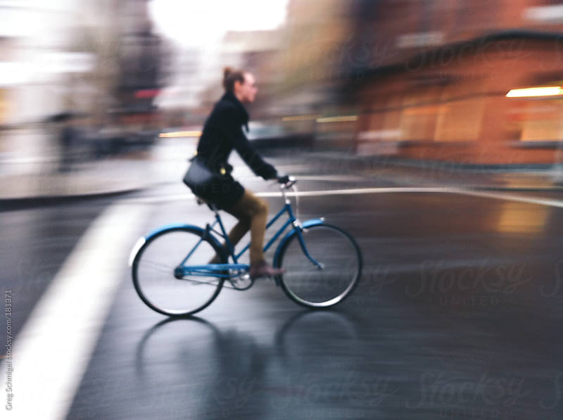 A woman riding a bicycle down a rainy city street. by Greg Schmigel for Stocksy United