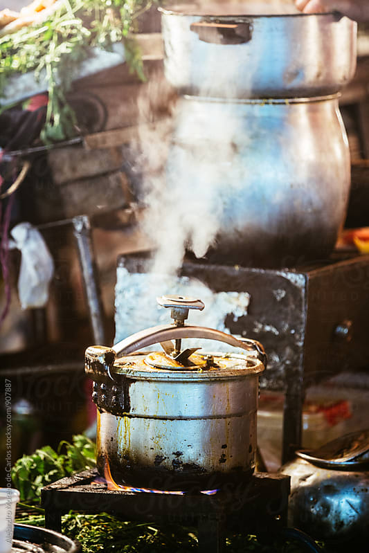 Pot in gas stove in a food stall with steam coming out by Alejandro Moreno de Carlos for Stocksy United