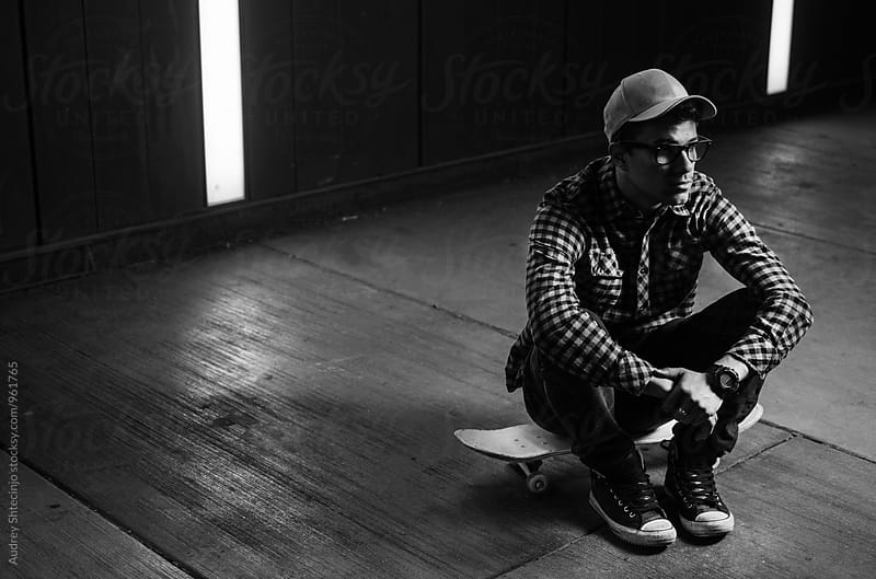 Portrait of young urban kid sitting on skate. by Marko Milanovic for Stocksy United