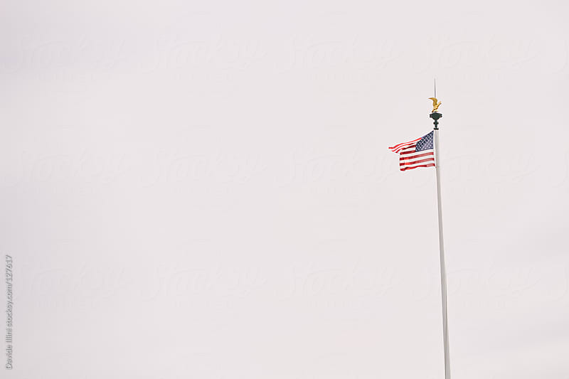 American flag on military cemetery - Omaha Beach, Normandy France. by Davide Illini for Stocksy United