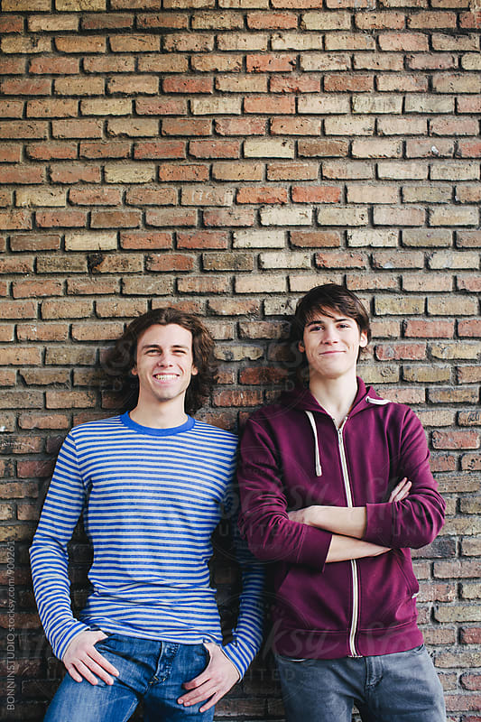 Portrait of teen friends standing in front of a brick wall. by BONNINSTUDIO for Stocksy United