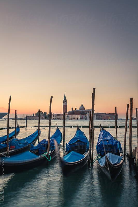 Venetian gondolas with the basilica san giorgio maggiore in the back by Leander Nardin for Stocksy United