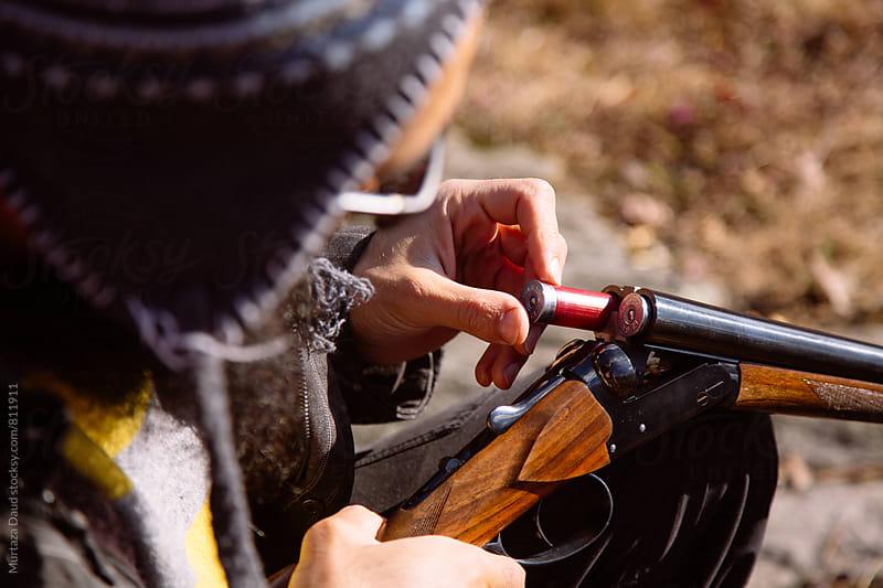 A model inserting a cartridge into a shotgun by Murtaza Daud for Stocksy United