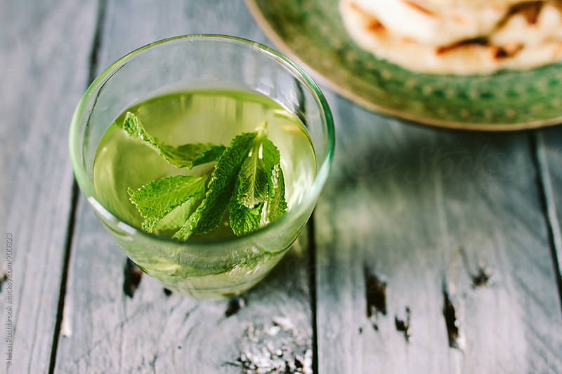 A glass of mint tea by Helen Rushbrook for Stocksy United