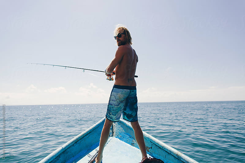 Man fishing at sea while standing on a boat. by Denni Van Huis for Stocksy United