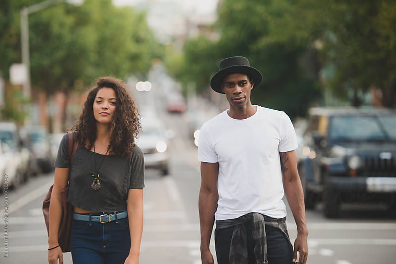 Couple standing in the street, looking at camera by Lauren Naefe for Stocksy United
