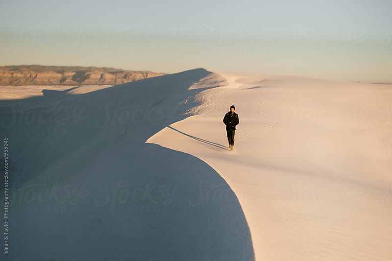 Man standing alone in desert landscape by Isaiah & Taylor Photography for Stocksy United