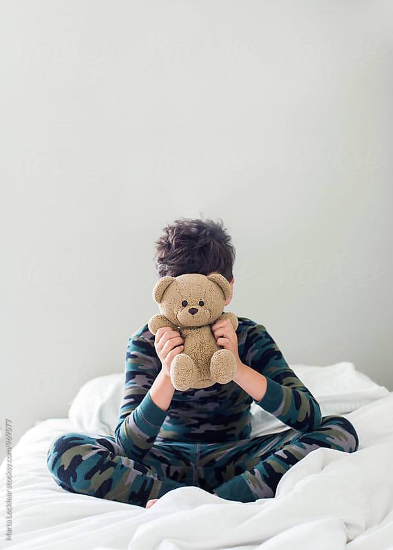 Boy hiding behind toy bear by Marta Locklear for Stocksy United