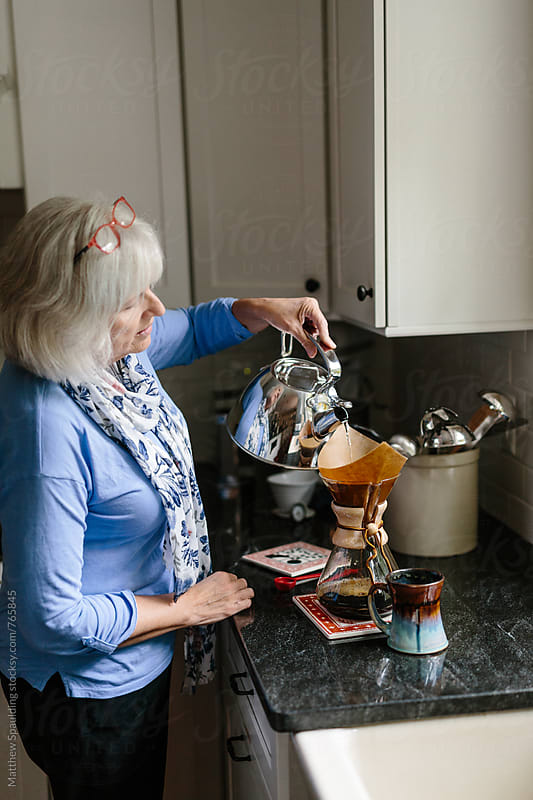 Woman pouring hot water over fresh coffee grounds by Matthew Spaulding for Stocksy United