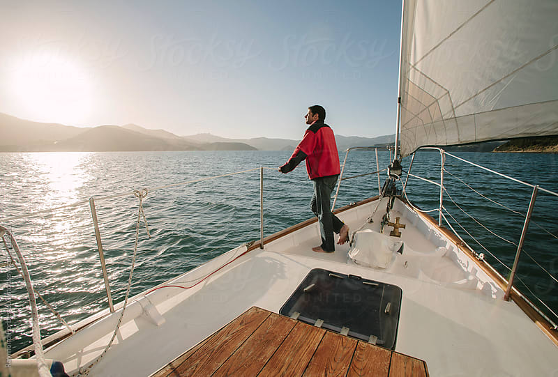 Sailor On Bow of Boat in Akaroa Harbor, New Zealand by Raymond Forbes LLC for Stocksy United