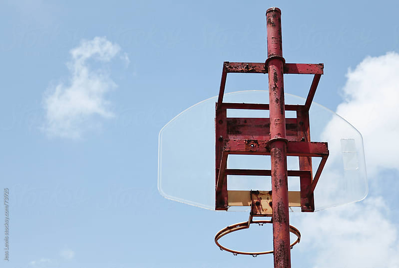 basketball hoop against blue sky by Jess Lewis for Stocksy United
