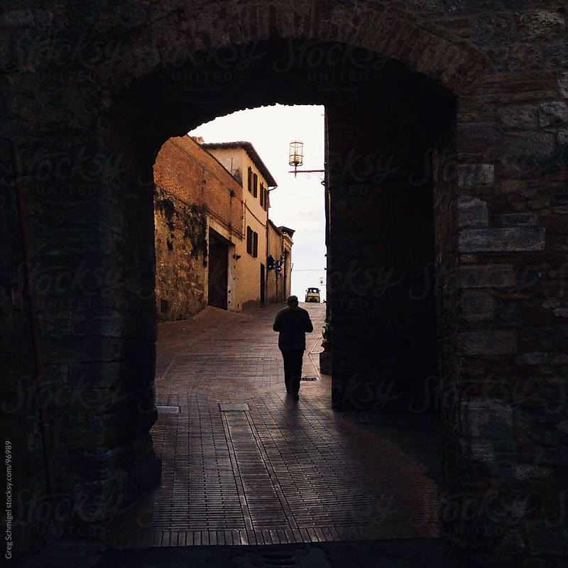 Man walking up hill through tunnel in Italy by Greg Schmigel for Stocksy United