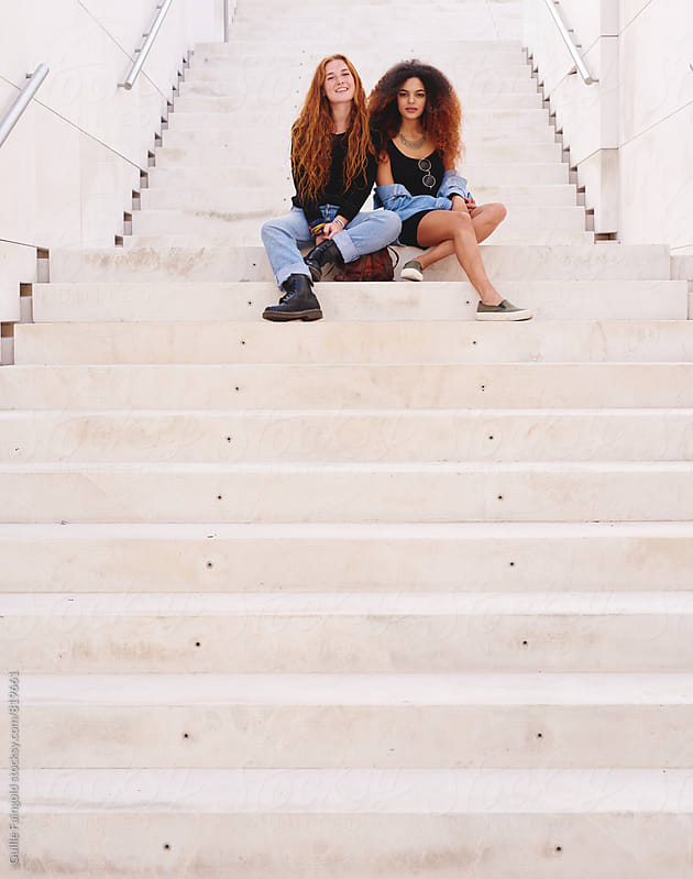 Two girlfriends sitting on stairs by Guille Faingold for Stocksy United