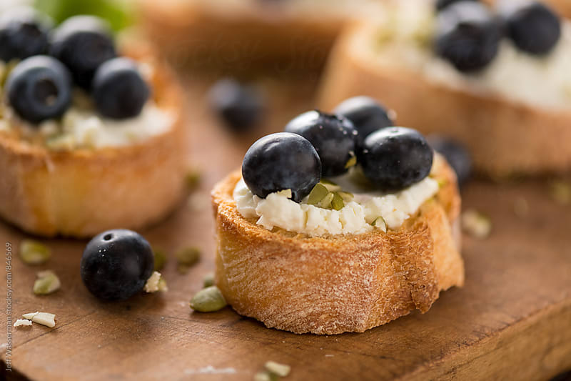 Crostini with Goats Cheese and Blueberry by Jeff Wasserman for Stocksy United