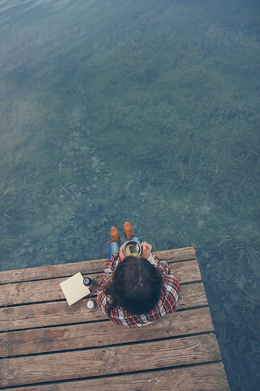 Aerial view of woman taking a tea at the lakeshore.  by BONNINSTUDIO for Stocksy United