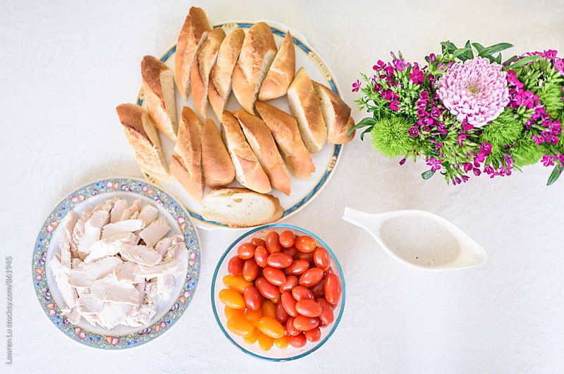 Bread, chicken, tomato, salad sauce and flower decoration by Lawren Lu for Stocksy United