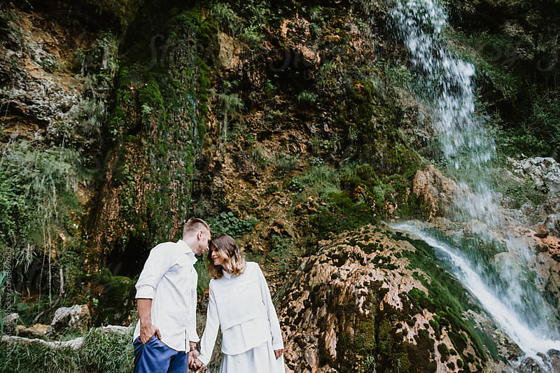 Beautiful young couple by the waterfall by Natasa Kukic for Stocksy United