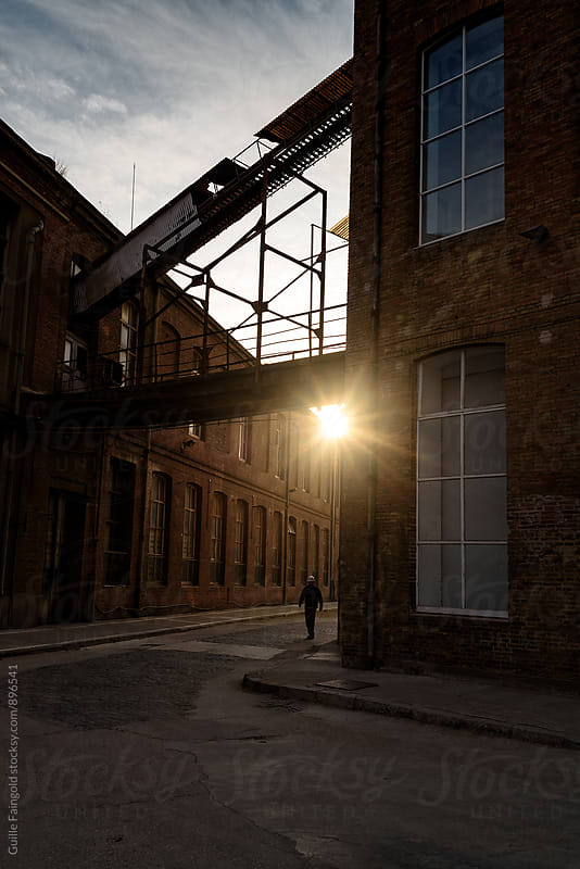 Unrecognizable man walking on the street near a factory at sunset by Guille Faingold for Stocksy United