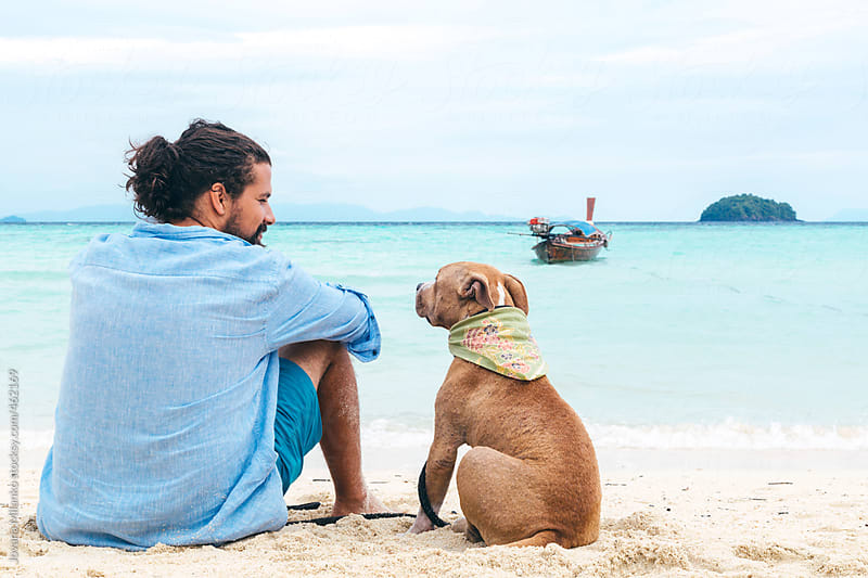 Dog and a man at the beach by Jovana Milanko for Stocksy United