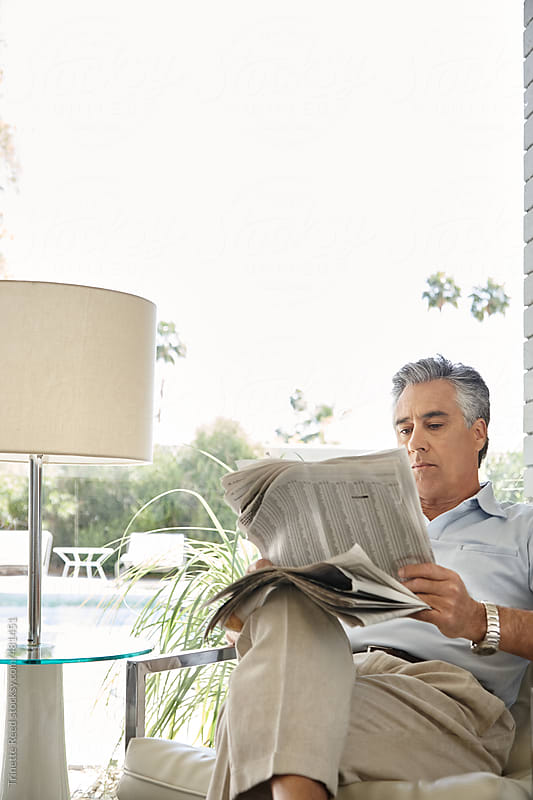 Mature Hispanic man reading the newspaper  by Trinette Reed for Stocksy United