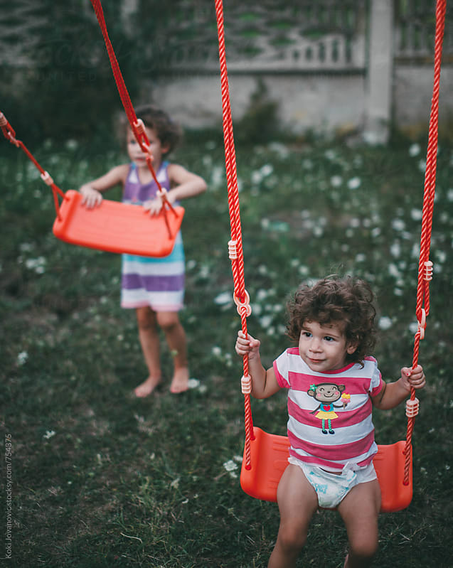 Two young girls playing in the backyard by Koki Jovanovic for Stocksy United